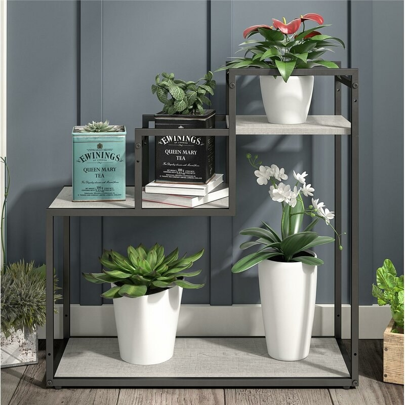 a plant stand with grey hardware and three marble shelves holding plants