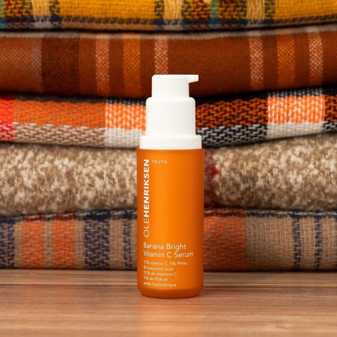 A bottle of face serum on a wooden table with a stack of folded blankets behind it