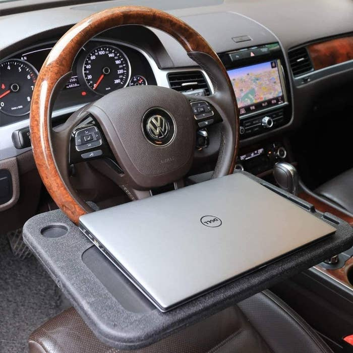 laptop on the tray which is attached to the steering wheel