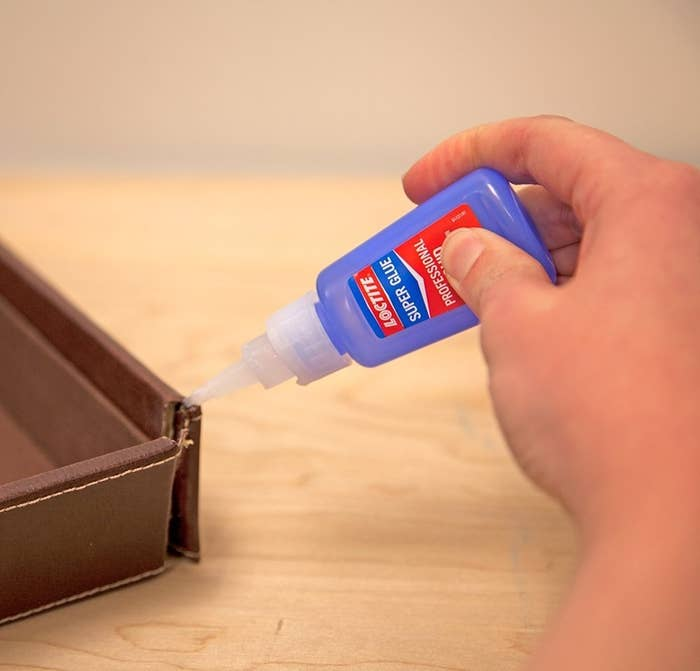 person using super glue to repair a tear in a brown leather item
