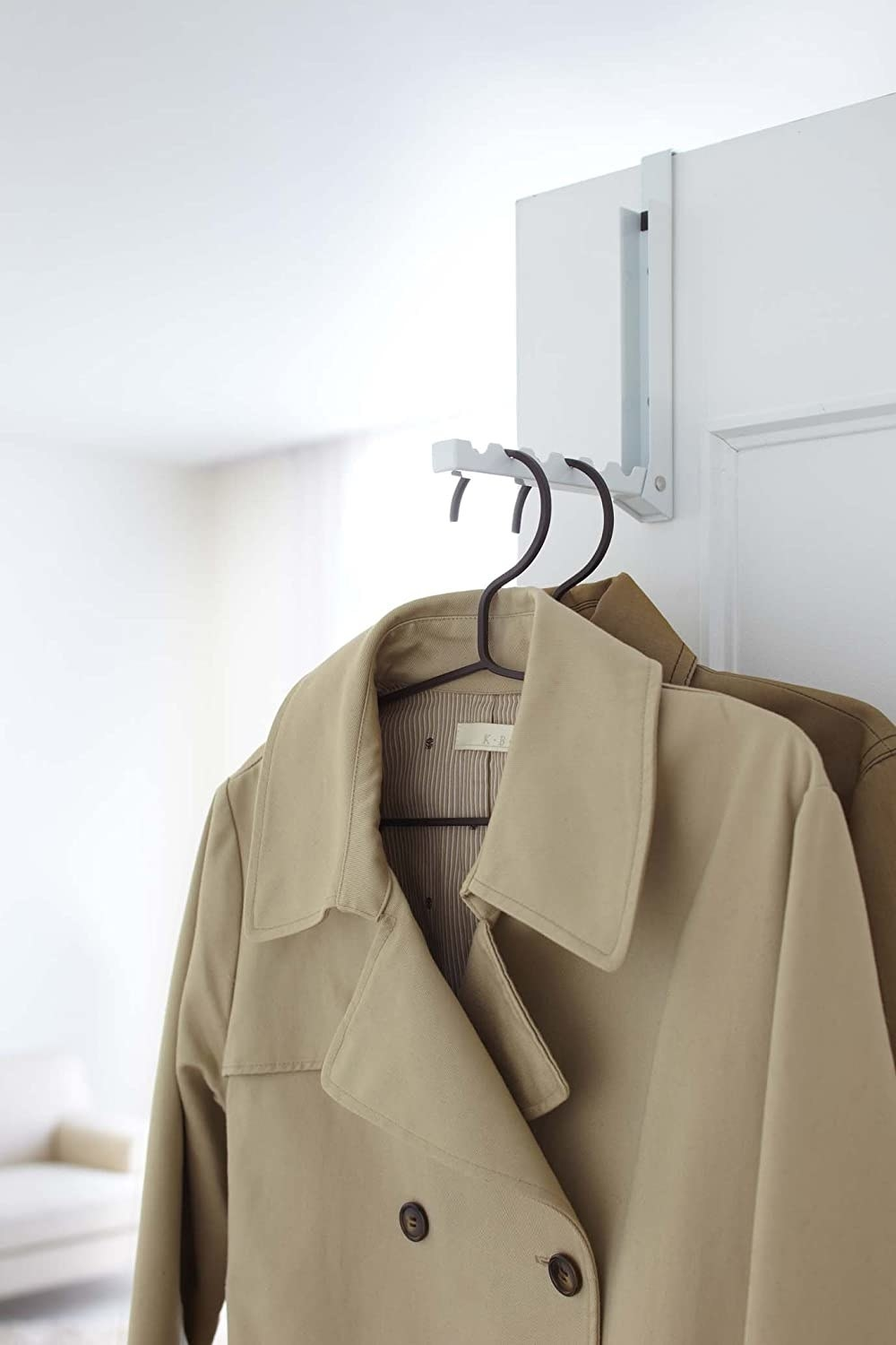A folding hook on a door frame holding several coats on clothes hangers
