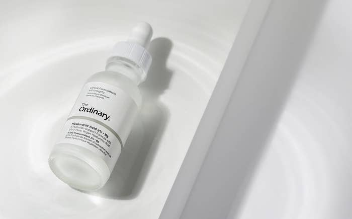 A small bottle of serum on a plain background