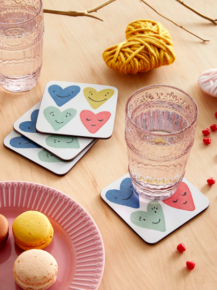 A set of four laminated cork coasters with smiling heart designs