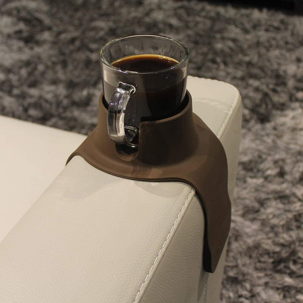 cup of dark liquid on the cup coaster on a couch arm