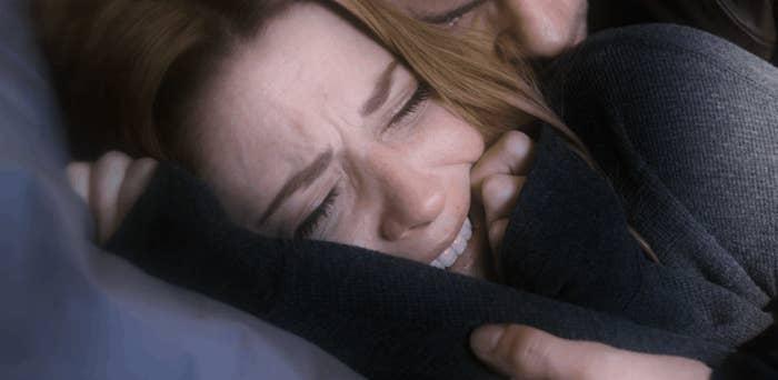Mel's husband holding her in a flashback image
