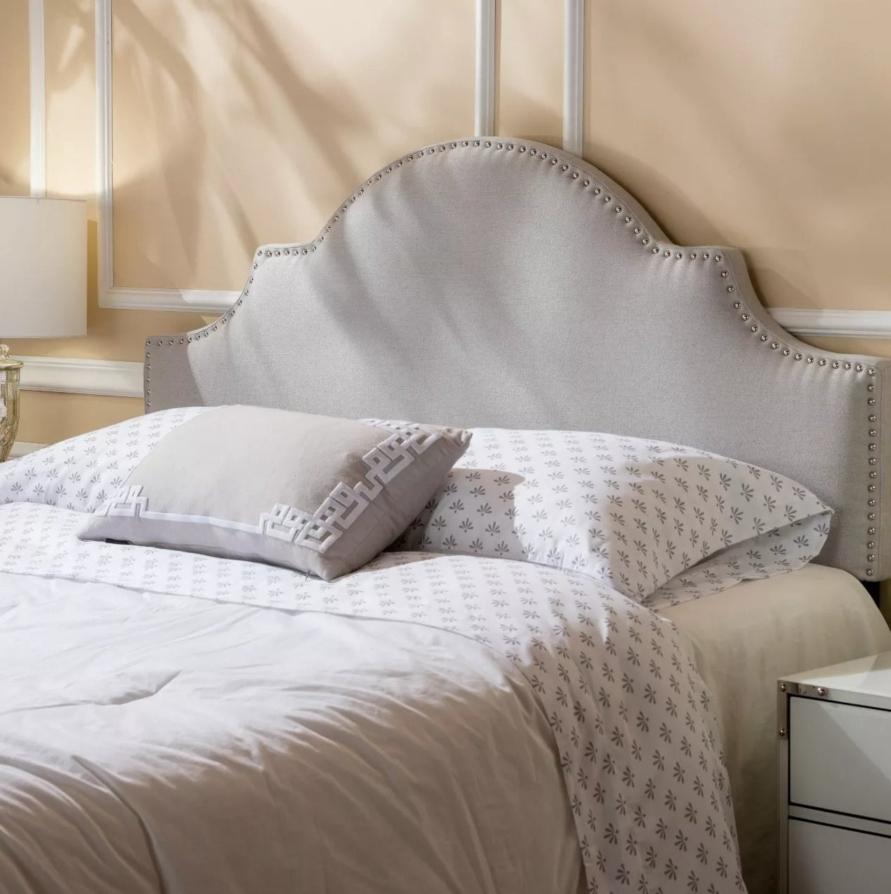 The upholstered headboard in light gray