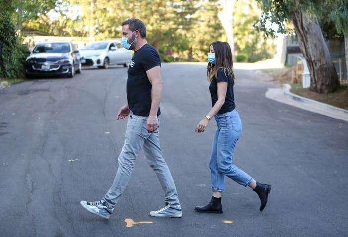 Ben Affleck and Ana de Armas are seen walking across the street in T-shirts, jeans, and face masks