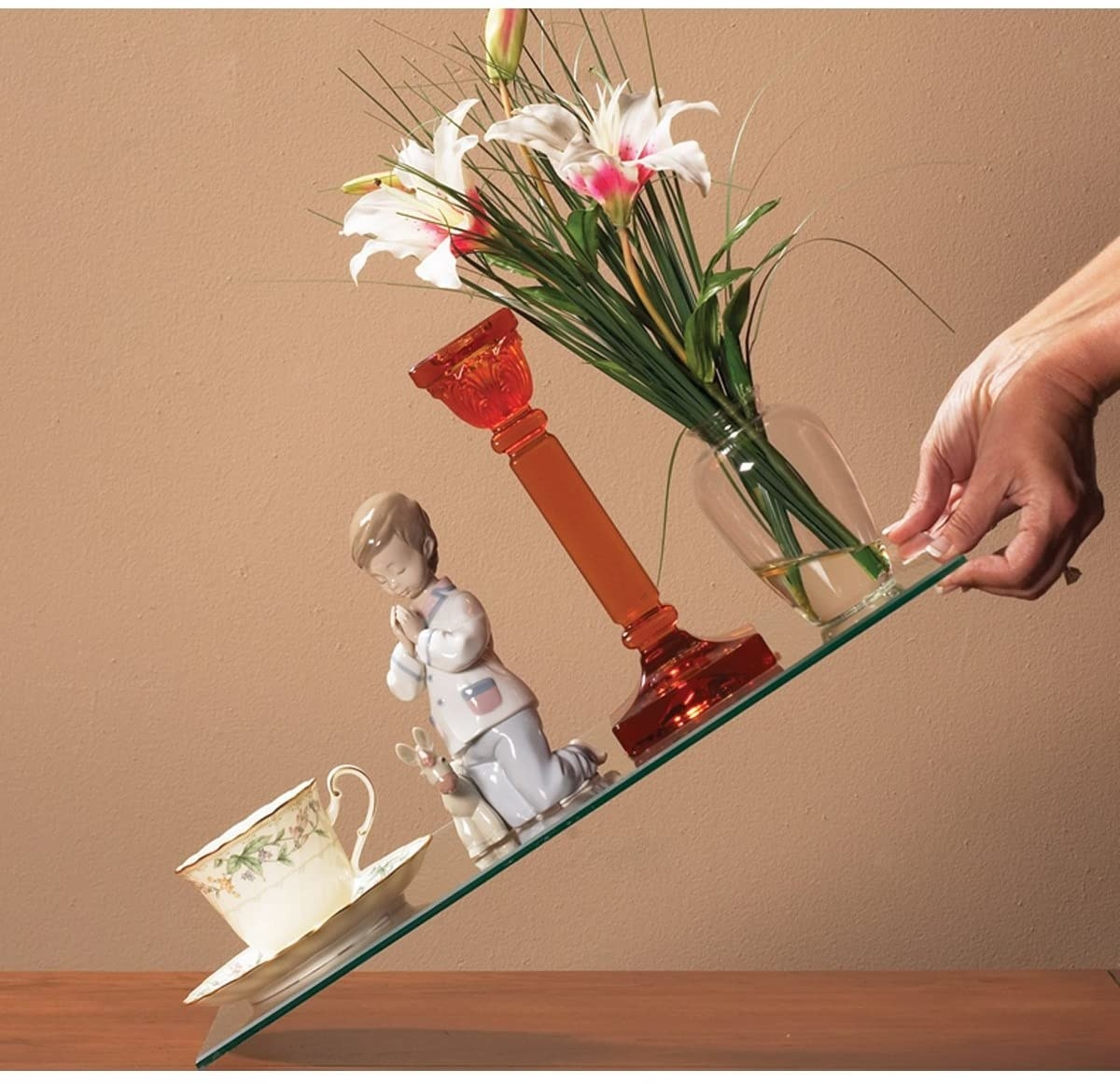 person holding a piece of glass at an angle that has a teacup, a porcelain doll, a candle holder, and a vase all secured so they don't fall