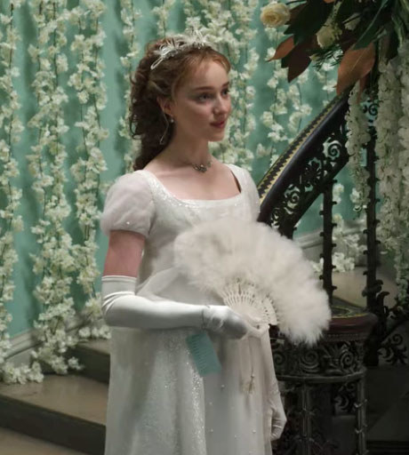 Daphne wears a glittery white gown and carries a feathered fan