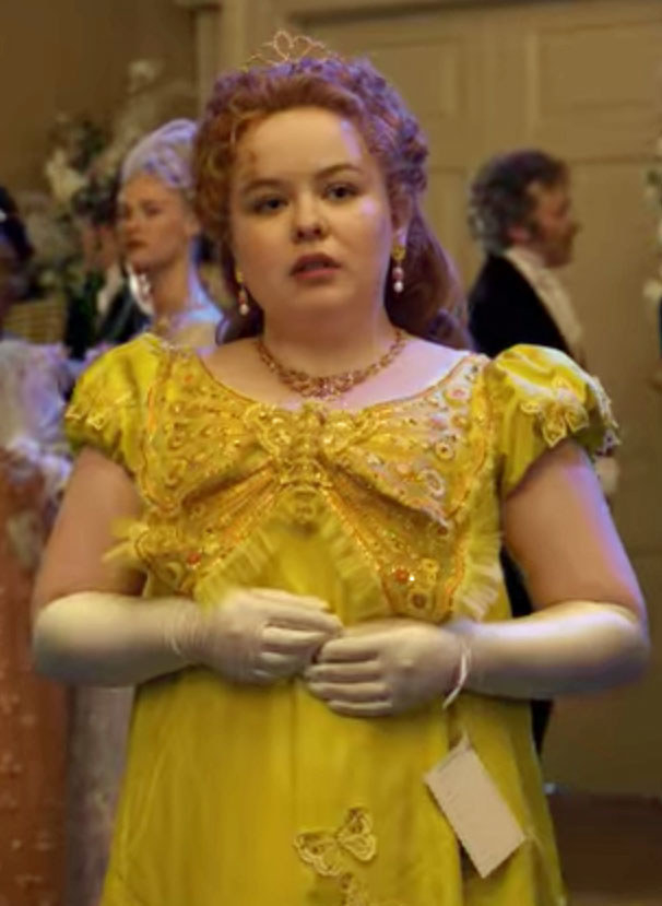 Penelope wears a dark yellow dress with a butterfly design on the front