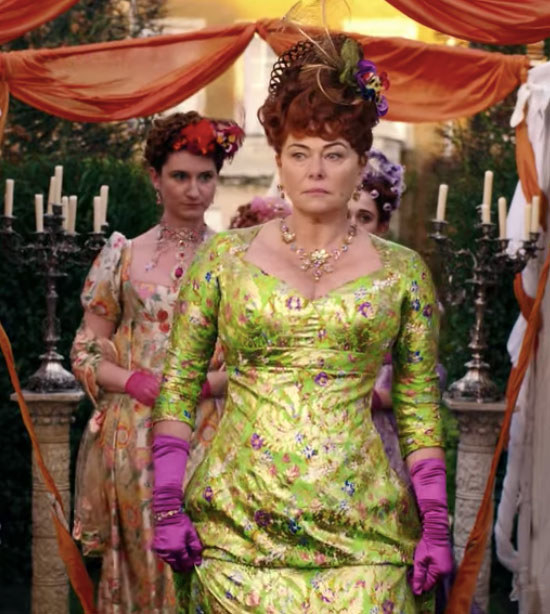 Lady Featherington wears a green gown and purple gloves