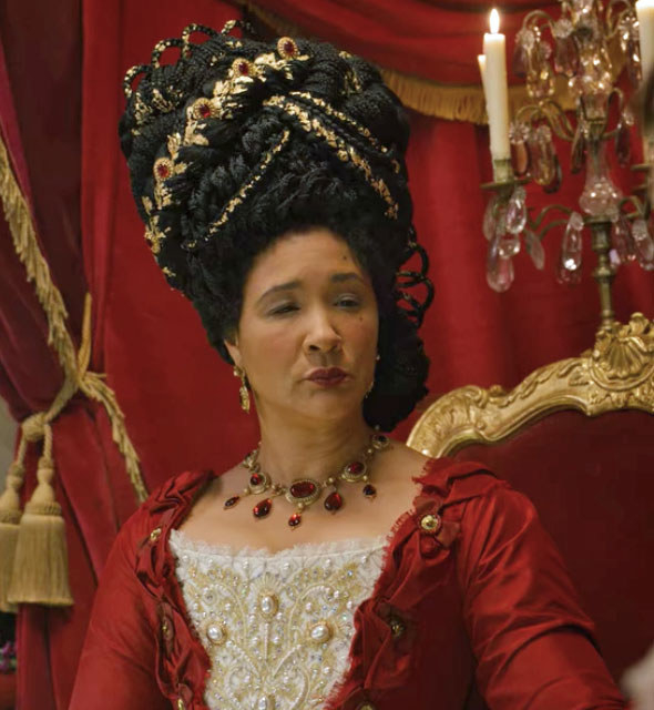 The queen weras a red gown and red and gold hair accessories