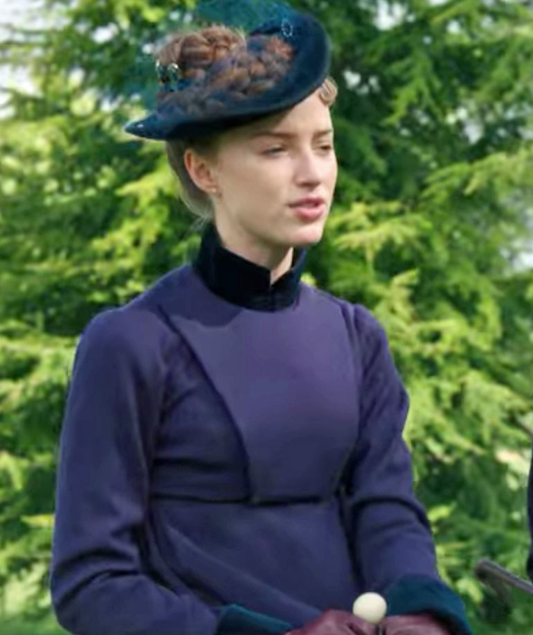 Daphne wears a dark blue riding coat and matching hat