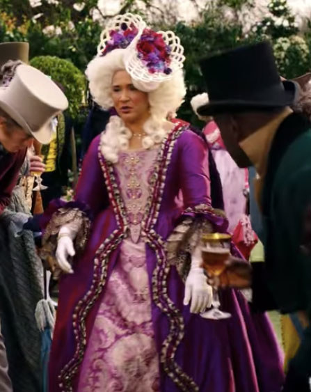 The queen wears an elaborate purple dress and headpiece