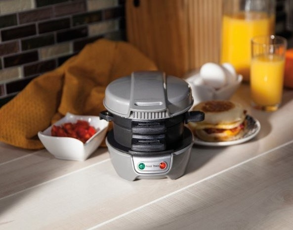 The sandwich maker on a countertop with a completed sandwich