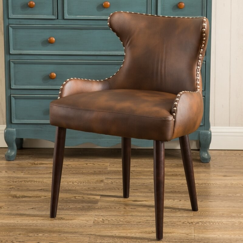 a brown leather desk chair with winged arms and wooden legs and bronze nail details.