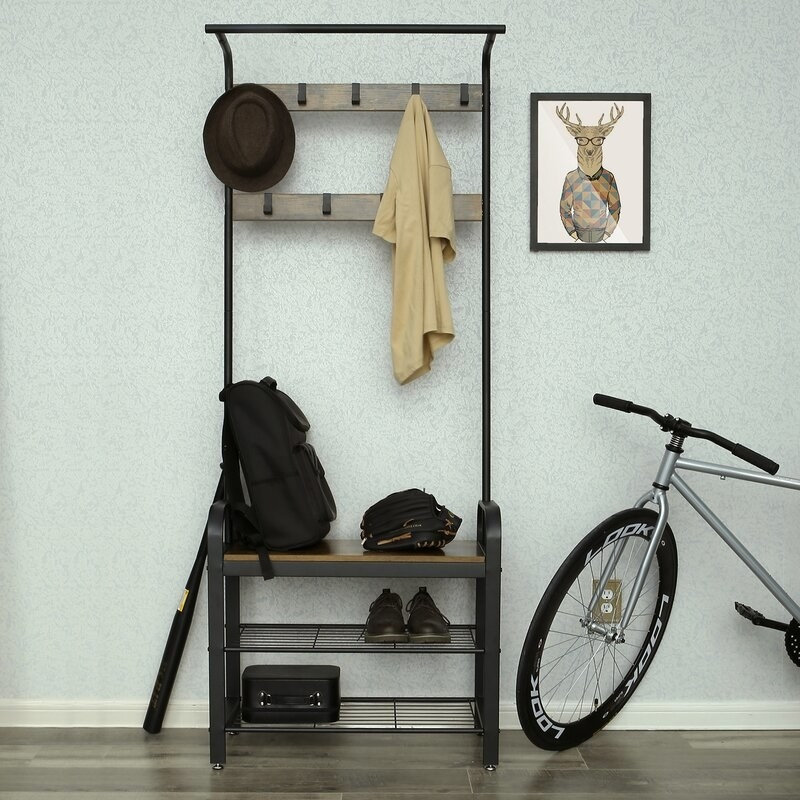a black and grey hall tree with two shoe shelves, one bench, and two rows of hooks