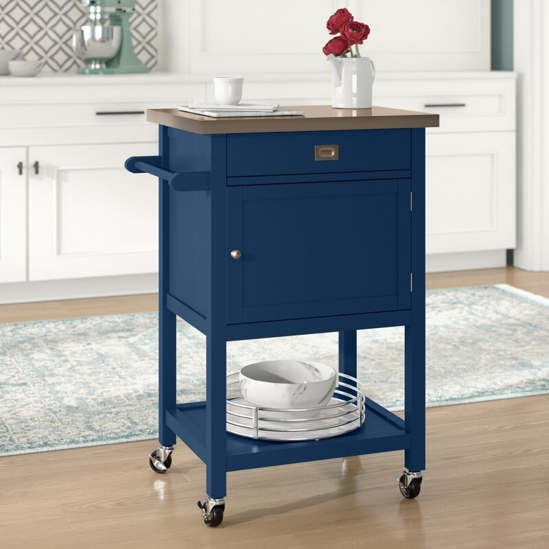 a blue kitchen cart with two drawers, a shelf, and a stainless steel top. this cart is on wheels