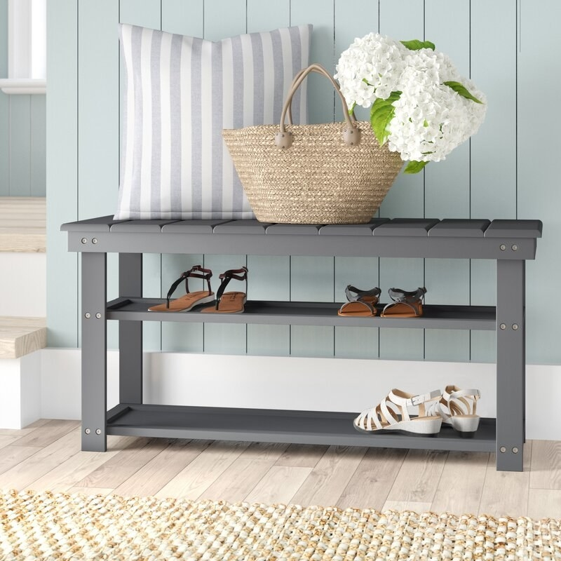 a grey wooden storage bench with two shelves holding shoes