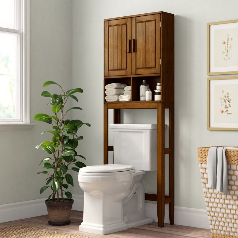 a brown wood over the toilet storage system with two cubbies and doors