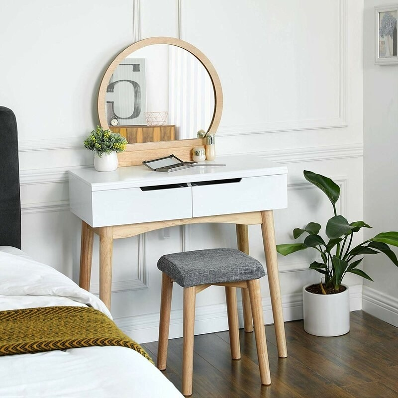 a white vanity with two drawers, wooden legs, a wooden round mirror, and a grey upholstered stool with wooden legs