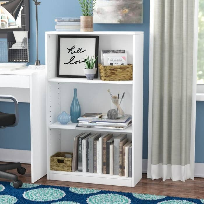 a white bookcase with three shelves, holding books, art and decor in a room