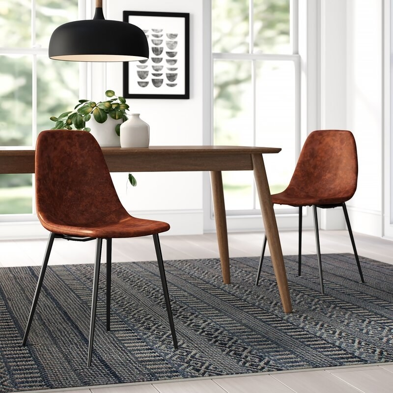 two tan leather chairs with black legs in a dining room