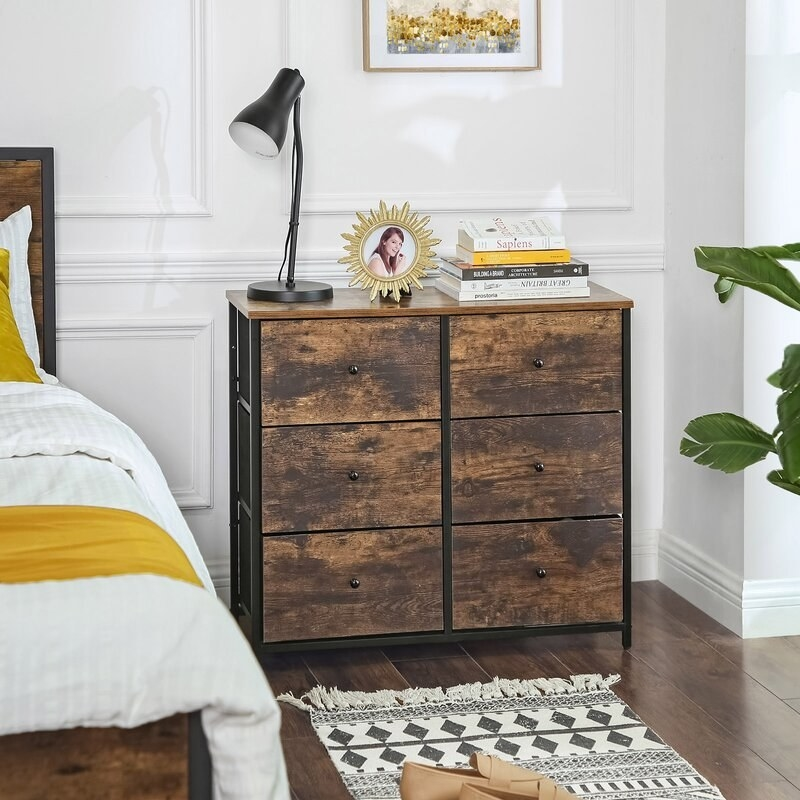 a black and brown dresser with six drawers