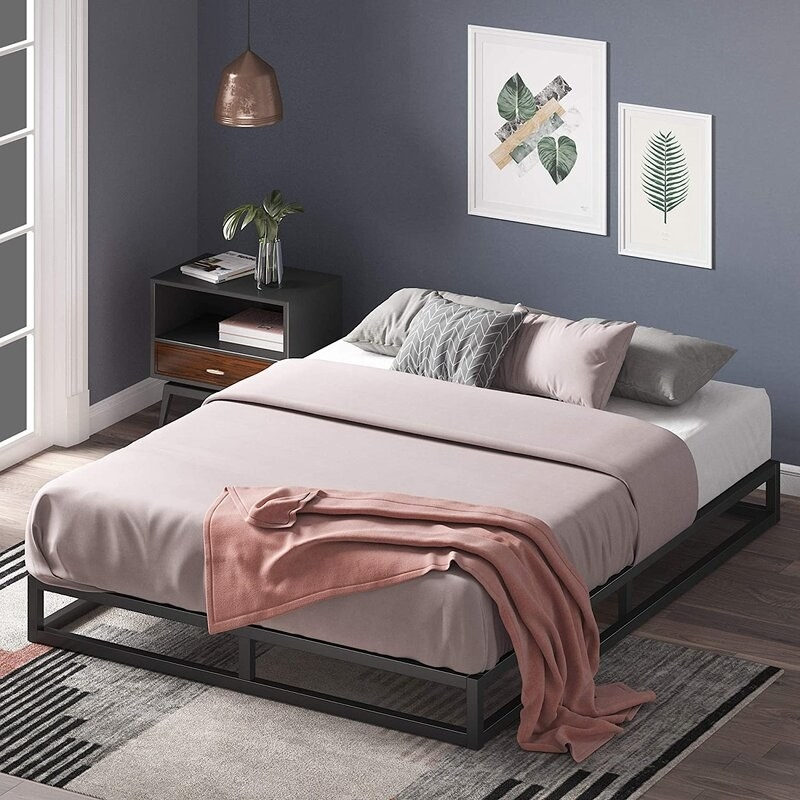 a black metal platform bed that is low to the ground, holding a bed