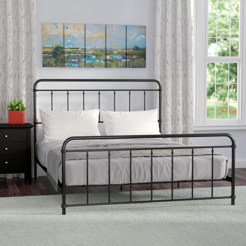 a black metal bed frame with a black metal headboard and footboard
