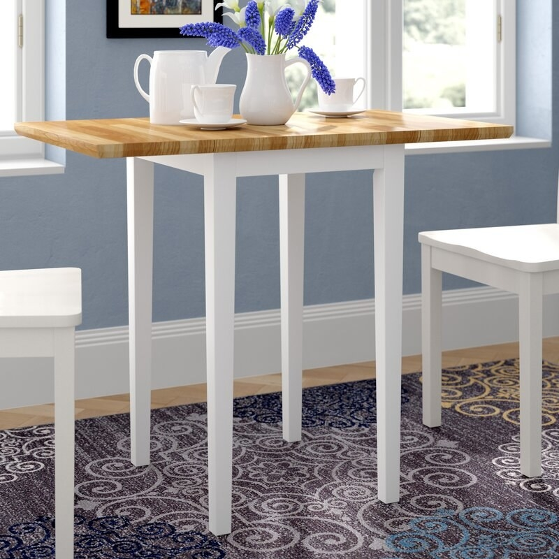 a wooden breakfast table with white legs in a kitchen