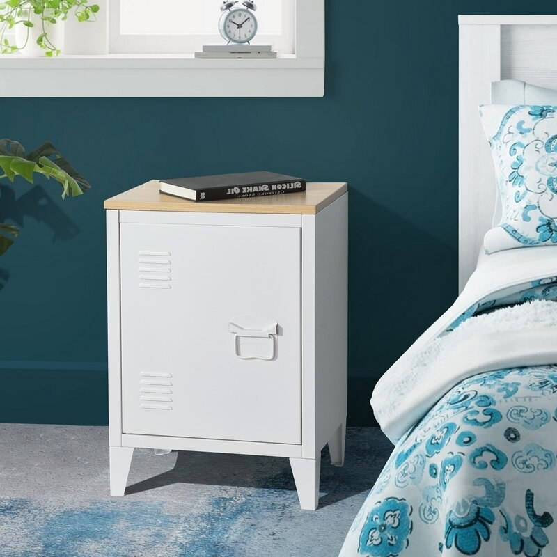a white and beige metal nightstand in a locker design next to a bed
