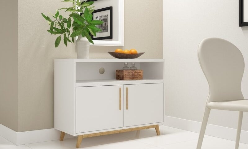 a white server drawer with two doors and a shelf, with wooden legs and handles