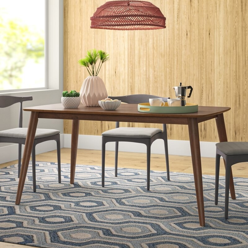 a brown dining room table with sleek legs in a dining room