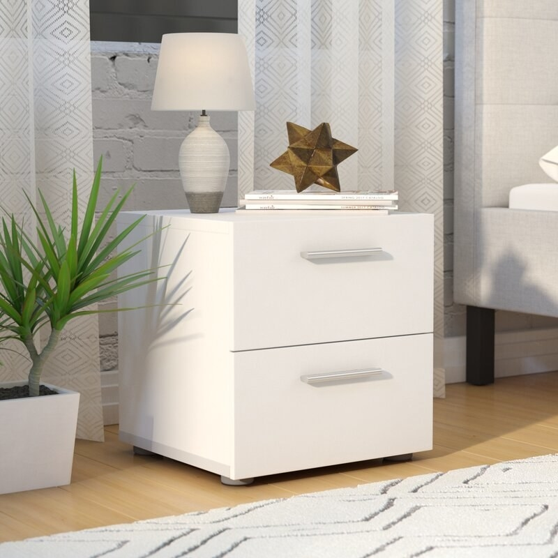 a white nightstand with two drawers and silver hardware