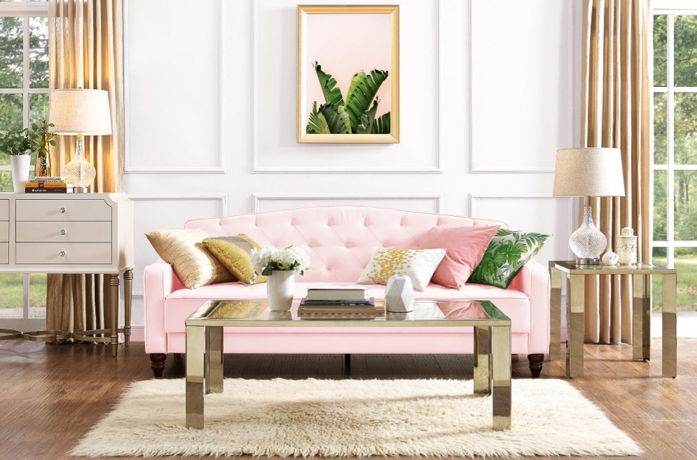 Pink velour couch with gold, green, white and pink pillows
