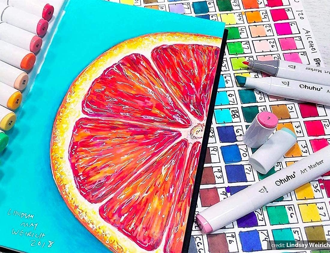 A few of the markers next to a vibrant illustration of a grapefruit slice