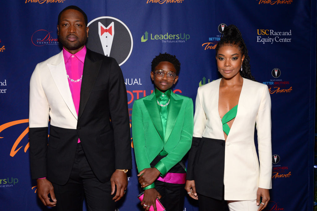 Dwyane and Gabrielle posing on a red carpet with their daughter Zaya