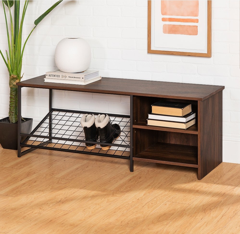 Dark wood entryway bench with black metal shoe rack and two side cubbies, white vase and books on top