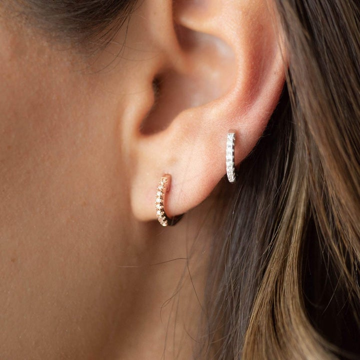Model wearing the gold and silver hoops in different piercings on one ear