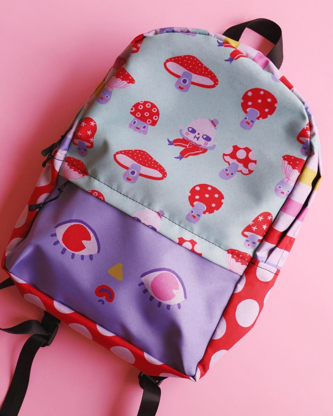 pastel backpack with face on the front pocket, rainbow stripes on sides, and mushrooms and humpy dumpty on the top front area