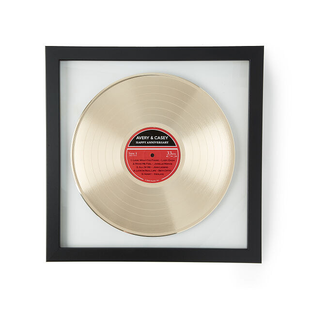 Gold metal record in a black frame with white matting