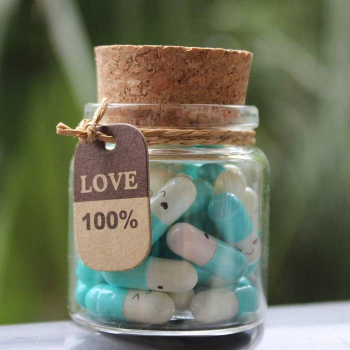 The corked bottle holding the blue capsules with a tag that says Love 100%