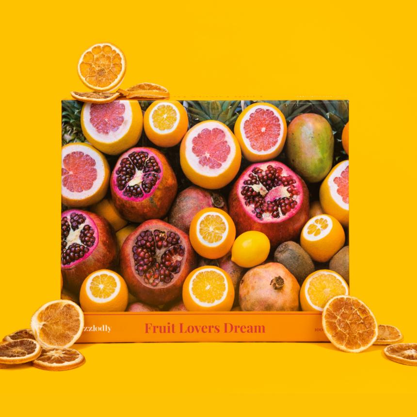 Puzzle with sliced and whole pomegranates, lemons, oranges, grapefruit, mango, and kiwi