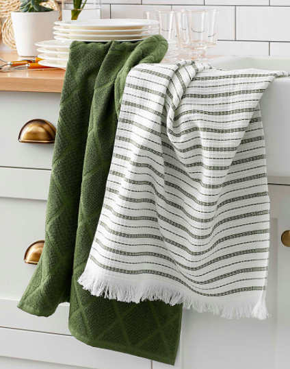 A pair of cotton tea towels draped neatly over the edge of a sink