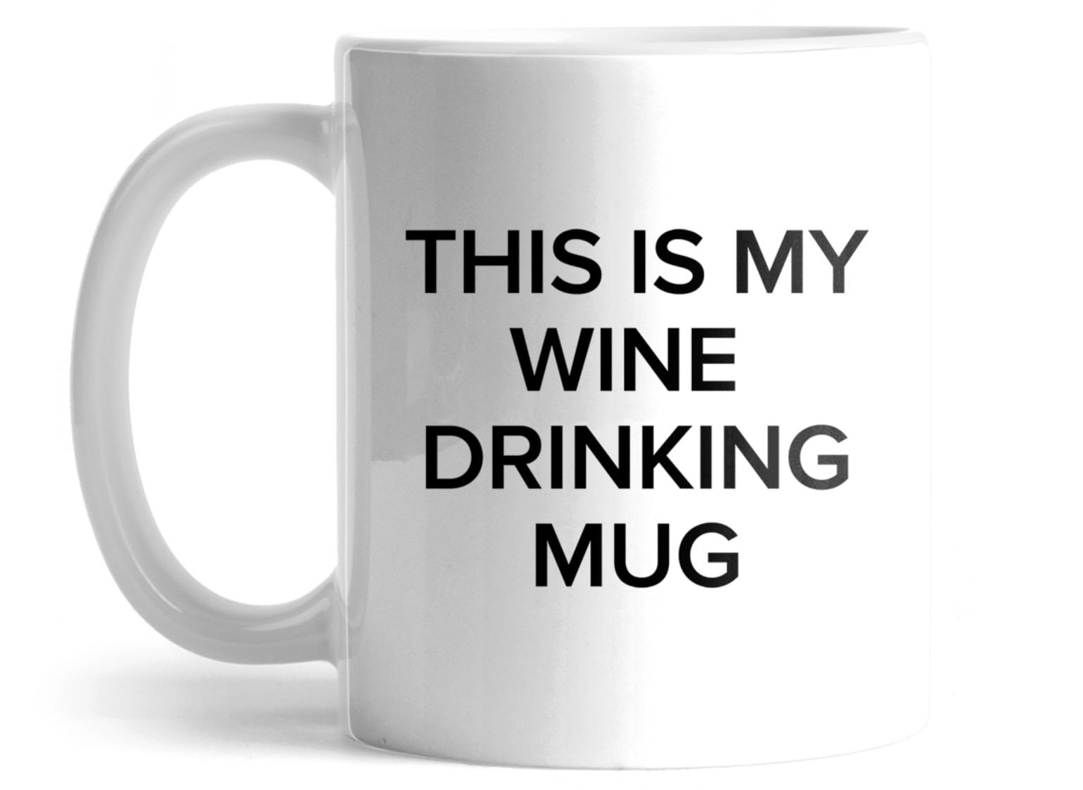 """the white mug with text that reads """"this is my wine drinking mug"""" in black text"""