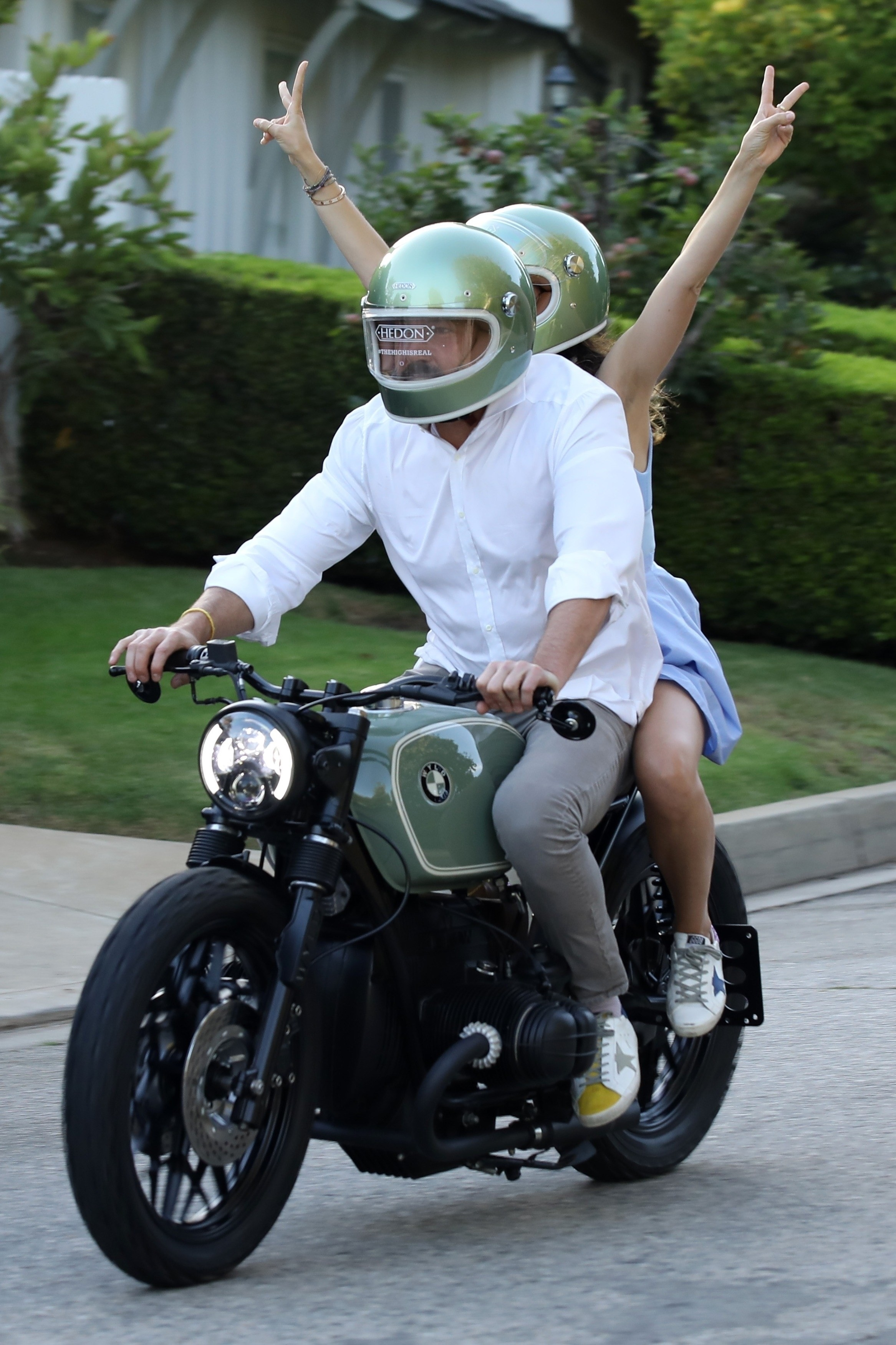 Ben Affleck and Ana de Armas riding a motorcycle as Ana holds both of her arms in the air and throwing the peace sign