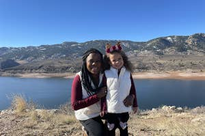 Melissa Burt poses with her young daughter in front of mountains and a lake.