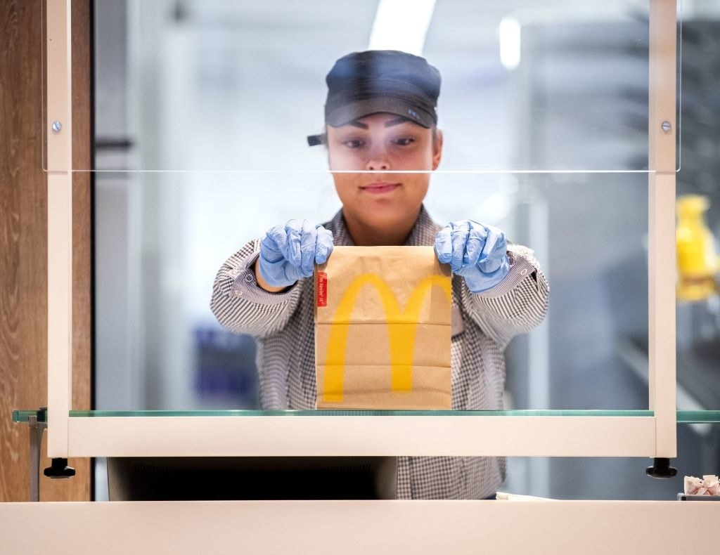 A McDonalds' employee holds up a food package at a test location in a restaurant in the Netherlands