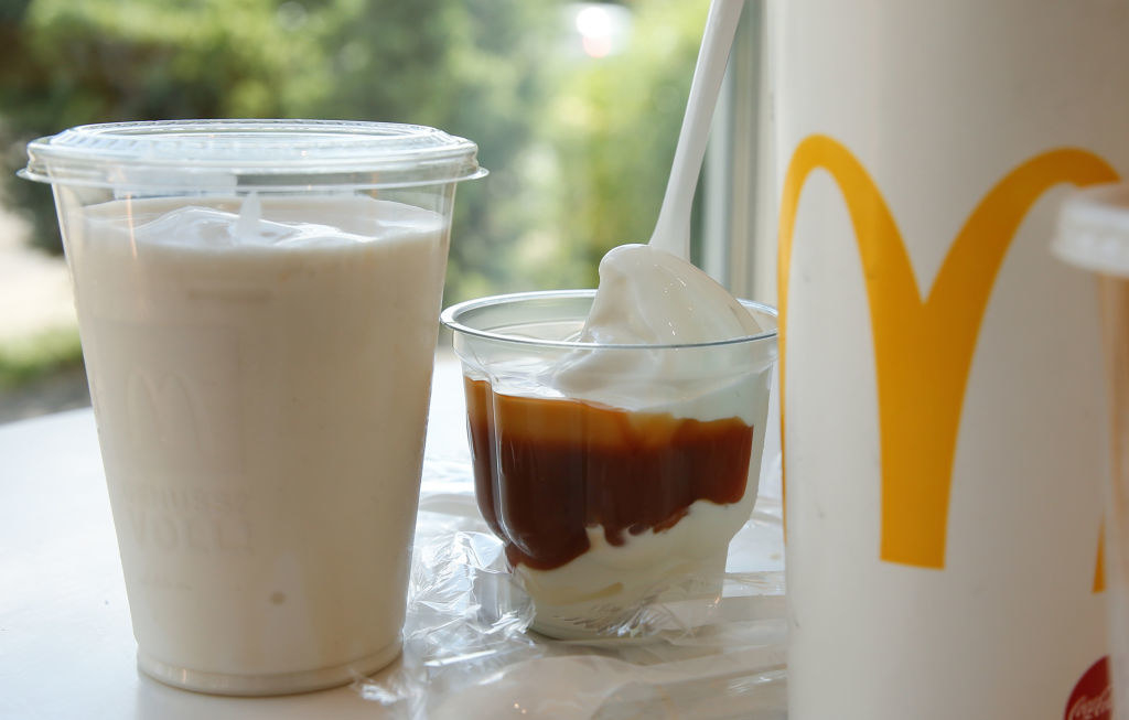 Plastic cup with a shake, a soft drink cup and a plastic cup with dessert on a table, taken in a McDonald's